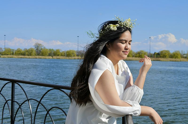 Woman with eyes closed standing by railing at river against blue sky