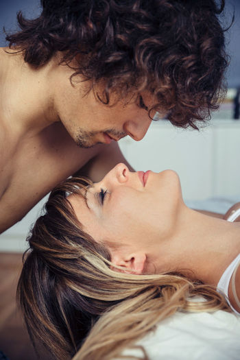 Profile of young man kissing to beautiful woman lying over a bed. Love and couple relationships concept. Bed Couple Intimate Kiss Love Man Relaxing Romance Romantic Woman Young Attractive Caucasian Closed Eyes Curly Hair Desire Female Liying Male Passion Portrait Sensuality Photo Sleep Togetherness Vertical