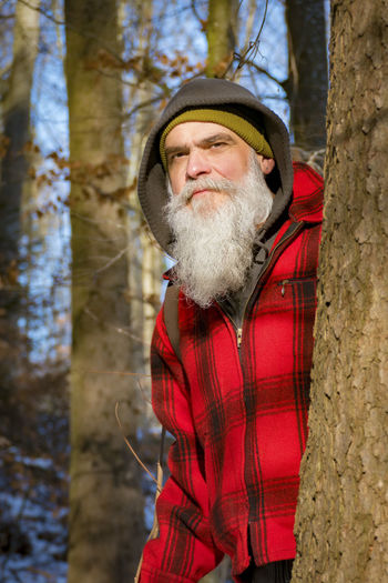 Portrait Of Bearded Man Standing By Tree At Forest
