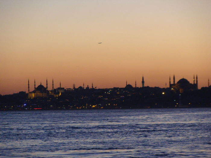 At sunset ... Istanbul skyline . With the Blue Mosque on the left and Hagia Sophia on the right across from each other and facing one another down Architecture Beauty In Nature Blue Mosque Istanbul Building Exterior Built Structure City Day Evening Falls Hagia Sophia Hagia Sophia On The Right And Blue Mosque On The Left Facing Each Other Down Istanbul Nautical Vessel On The Bosphorus Outdoors Scenics Silhouette Sky Sunset Transportation Travel Travel Destinations Turkey Water ıstanbul