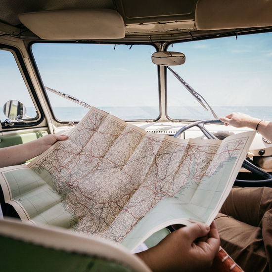 Couple reading South Devon map in Campervan 1960s Camping Devon Devon UK Driving Map Old Map Path Retro Campervan Close-up England Human Hand Map Reading Mode Of Transport Real People Searching Sky Transportation Uk Vintage Volkswagen