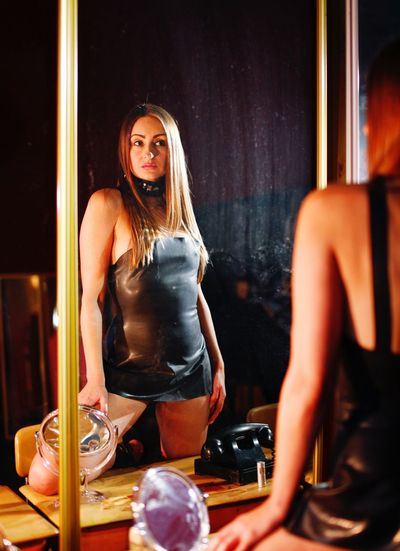 Mid adult woman standing in front of mirror at nightclub