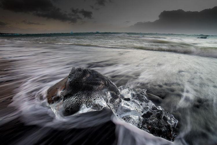 Close-up of sea wave splashing on beach against sky