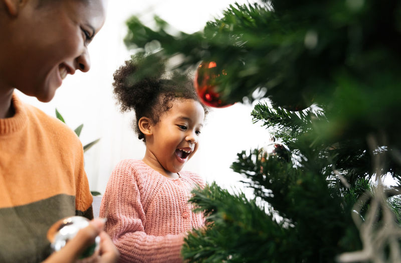 Mother and daughter holding decoration on christmas tree