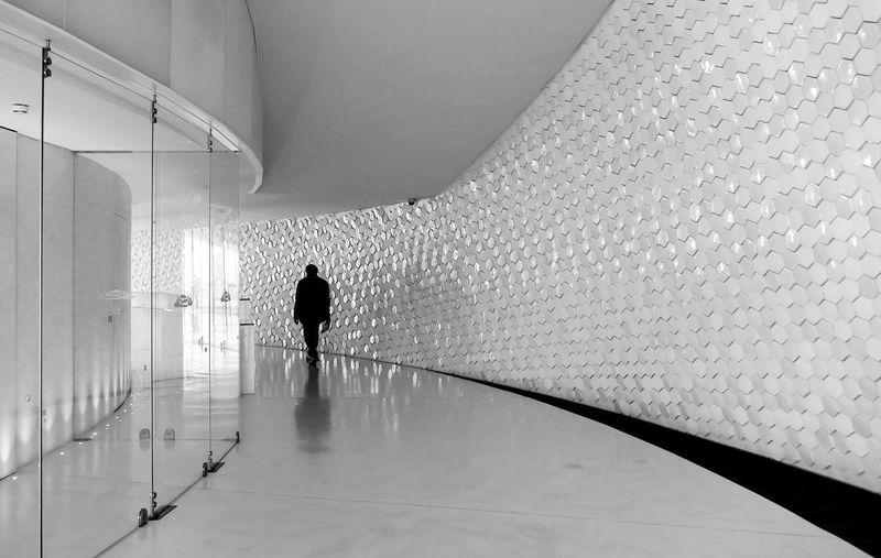 Rear view of silhouette woman walking in corridor