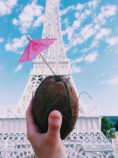 Cropped hand holding coconut against replica eiffel tower