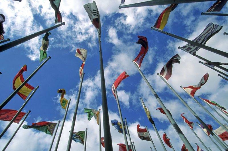Low angle view of flags waving on pole against sky