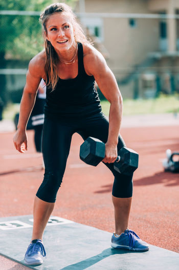 Woman lifting dumbbell on running track