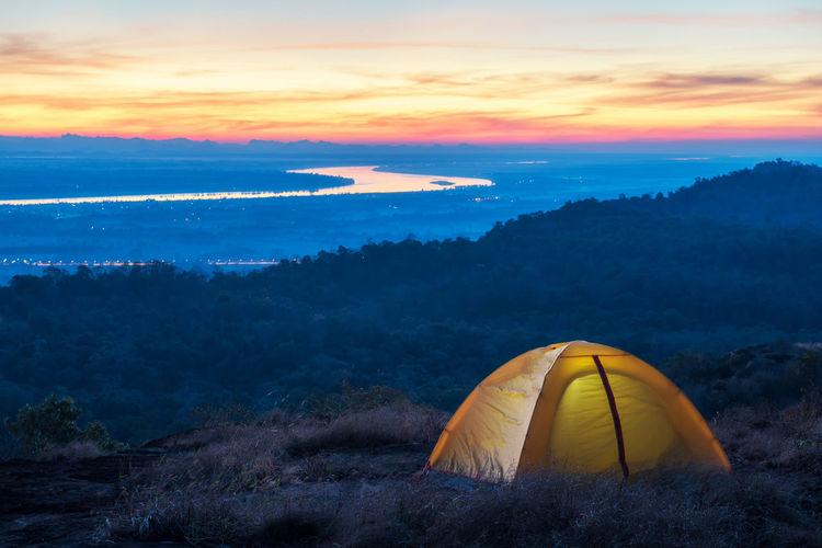 Illuminated tent on field against sky at sunset