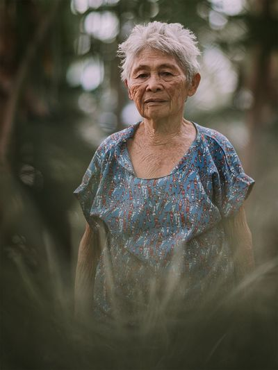 Portrait of senior woman seen through plants