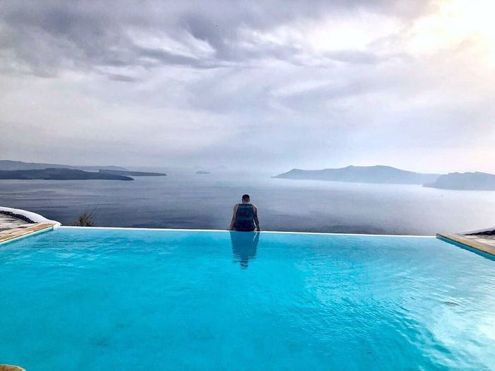 Rear view of man standing in swimming pool against sky