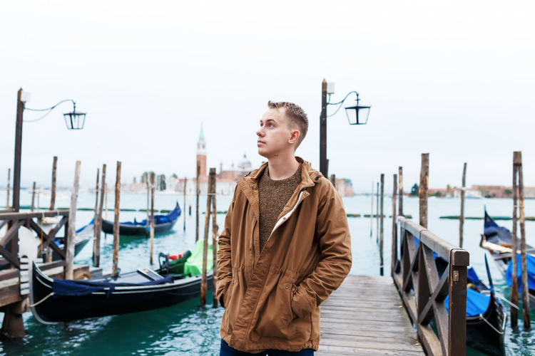 Young man standing in boat against sky