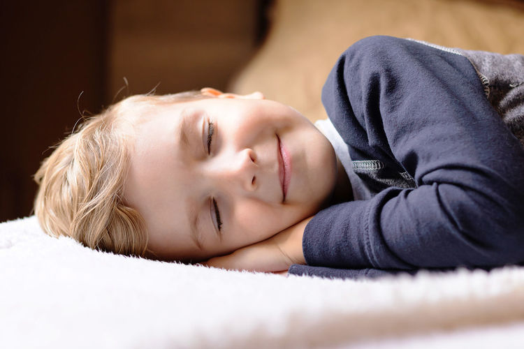 Close-up portrait of boy lying on bed at home