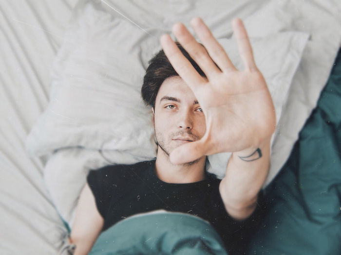 High Angle View Of Man Gesturing Stop While Lying On Bed At Home