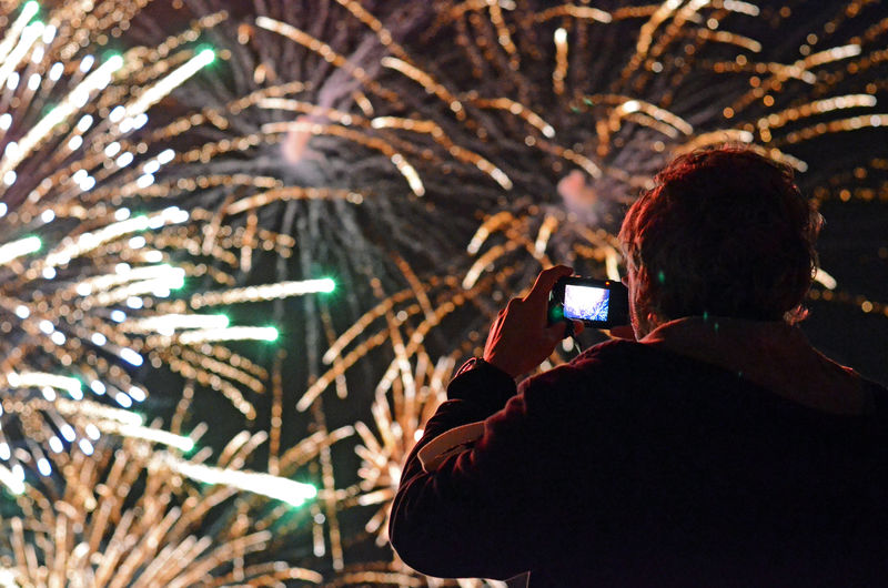 Rear View Of Man Photographing Fireworks At Night