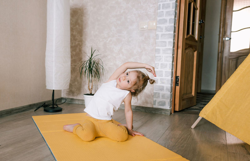Girl sitting on wooden floor at home