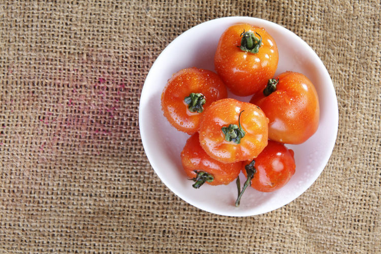 High Angle View Of Tomatoes In Plate On Burlap