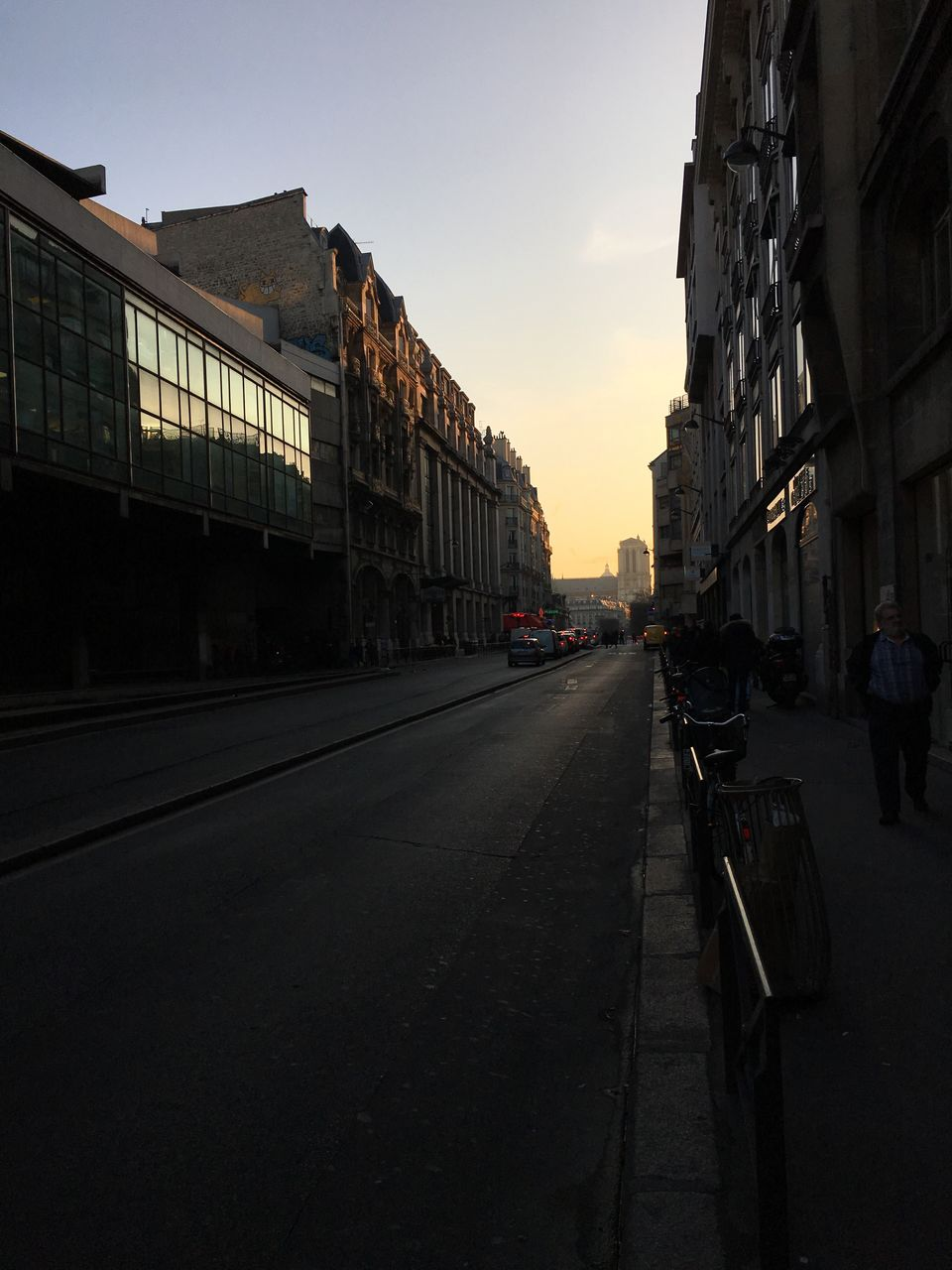 architecture, built structure, building exterior, transportation, land vehicle, city, street, road, sunset, car, mode of transport, outdoors, sky, real people, day
