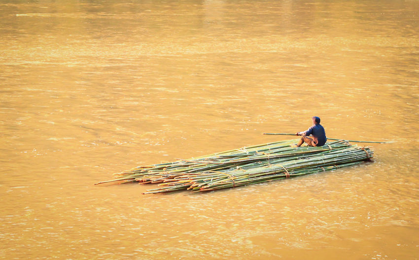 Rear view of man on wooden raft amidst river