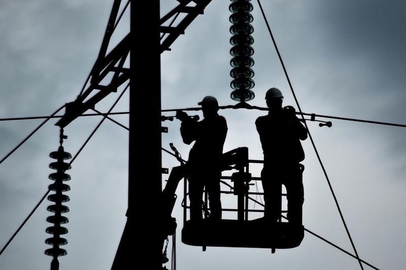 Silhouette workers on cherry picker by electricity pylon against sky