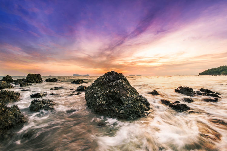 Rocks at beach against cloudy sky during sunset