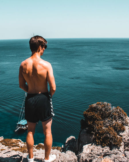 Rear view of shirtless man looking at sea against sky