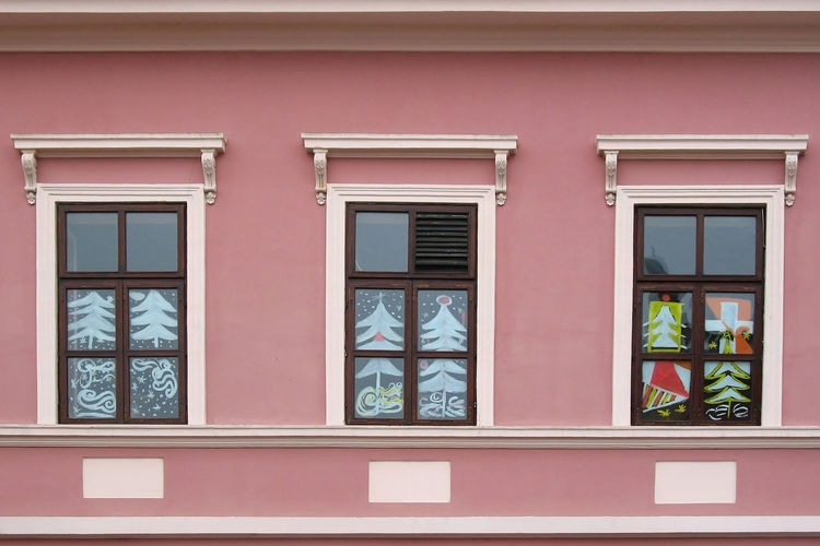 Three windows with christmas painting decoration on the pink wall