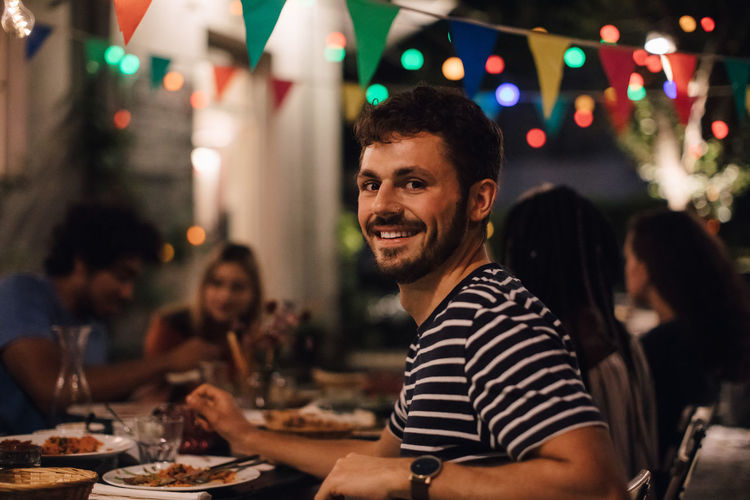 Portrait of smiling young man having dinner with friends during garden party