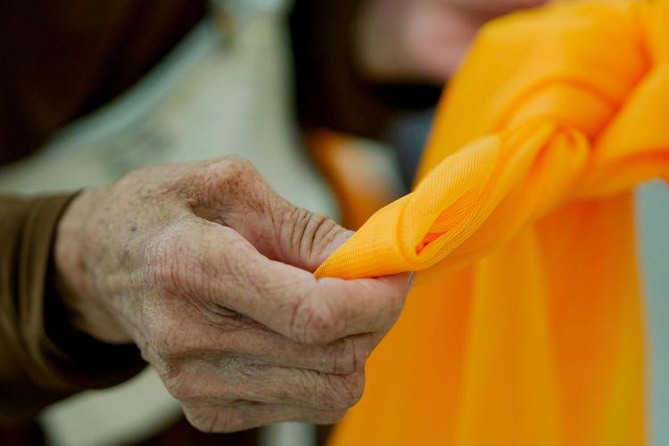 Close-up of hand holding orange textile