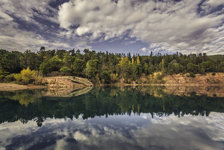 Autumn mirror reflection into the water of Carces lake, somewhere in Provence, France. Beauty In Nature Cloud - Sky Dramatic Sky At Sunset Time Forest From A Tourist Perspective Lake Landscape Betterlandscapes Miles Away Outdoors Pinaceae Pine Forest Reflection On Water Pine Tree Pine Woodland Provence Reflection Reflection Lake Scenics Sky EyeEm Best Shots Water Water Mirror Water Mirror Reflection Of Pine Forest Water Reflection Of Pine Forest Natural Mirror