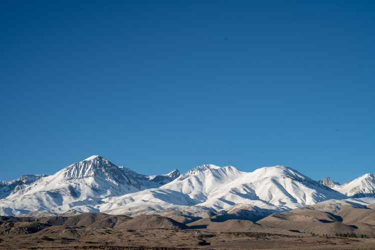 Scenic view of snowcapped mountains against clear blue sky