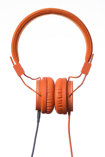 Orange Headphones on white Background Cable Close-up Communication Computer Computer Cable Computer Network Connection Headphones Internet Network Connection Plug No People Product Product Photography Sound Technology White Background