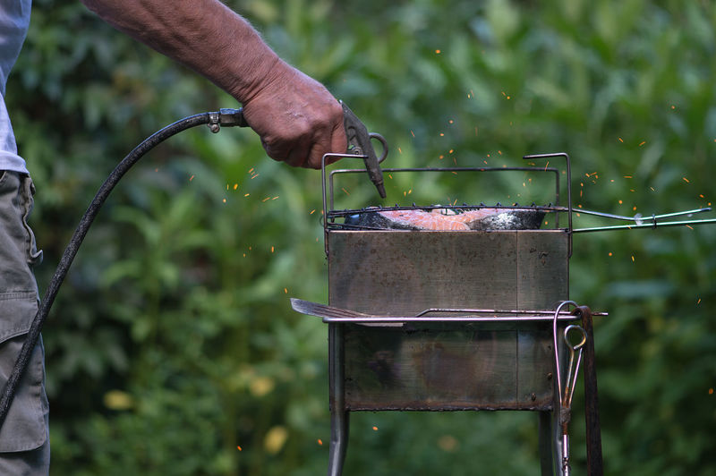 Midsection Of Man Blowing Barbecue Grill With Equipment While Preparing Food