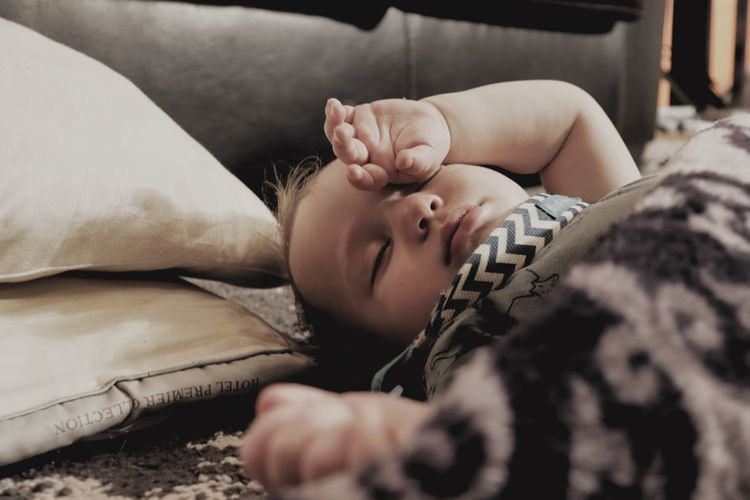 A small baby sleeps on the floor after a enjoying a fun afternoon play session.