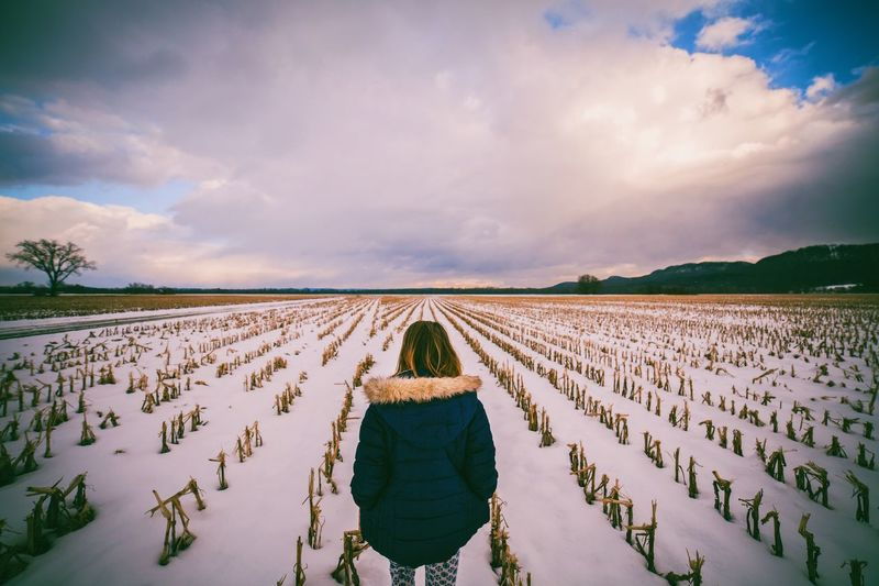 Rear view of girl on agricultural field during winter