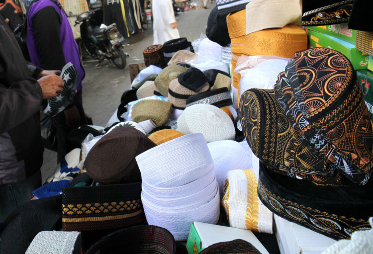 Midsection Of Men Selling Skull Caps At Market Stall