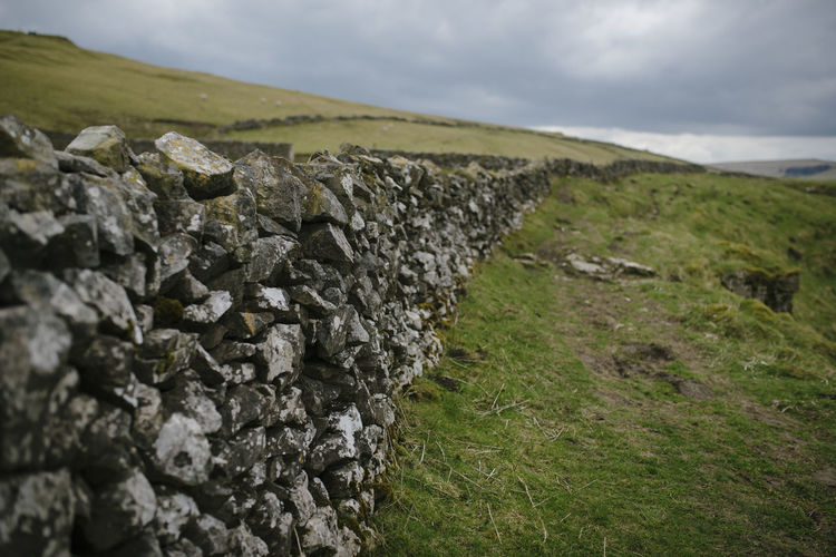 Stone wall on landscape against cloudy sky