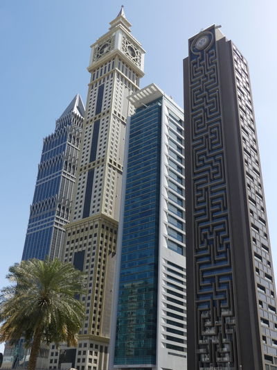 Skyscrapers including Evor Hotel (second from left) onSheik Zayed Road, Dubai, United Arab Emirates 2019 Dubai UAE 2019 Sheik Zayed Road Blue Sky Palm Tree Low Angle View No People Tall - High City Luxury Skyscrapers Towers Tower Blocks Modern Architecture Modern Design Glass And Steel Structures Modern Architecture Tropical Climate Full Frame Composition Outdoor Photography Buildings Tourist Destination