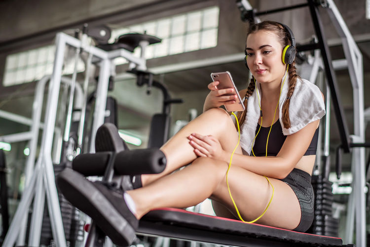 Young woman listening to music while sitting in gym