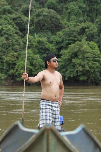Full length of shirtless man standing in lake against trees