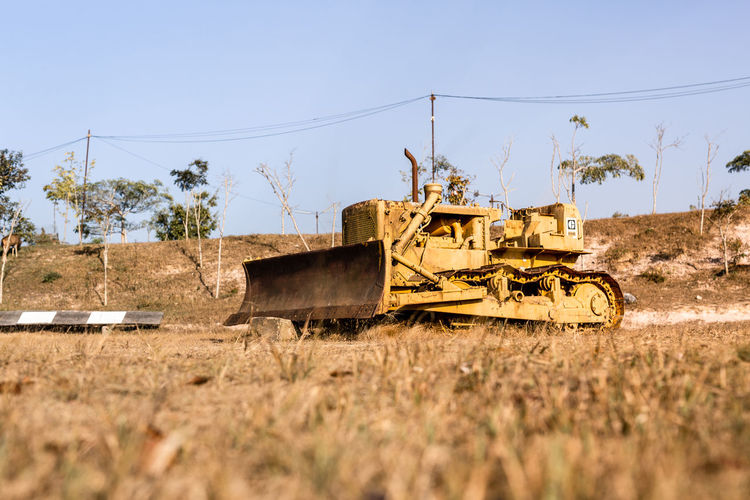 Unuse bulldozer at Khao yai. Sky Field Land Nature Day Transportation Land Vehicle Plant Machinery Clear Sky No People Mode Of Transportation Tree Outdoors Tracktor Argriculture Field Landscape Farm Equipment Machinery Yellow Bulldozer Old