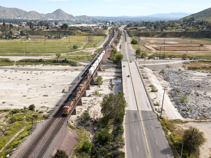 Colton, CA / USA - 4/07/2019: A BNSF Intermodal Train awaits a signal in Colton. Transportation Road Day High Angle View Nature Mountain Built Structure Direction Architecture Environment No People The Way Forward Plant Outdoors Mode Of Transportation Connection Car Landscape Motor Vehicle Land Vehicle Train Railroad Intermodal Freight Transportation Overhead View Top Down View