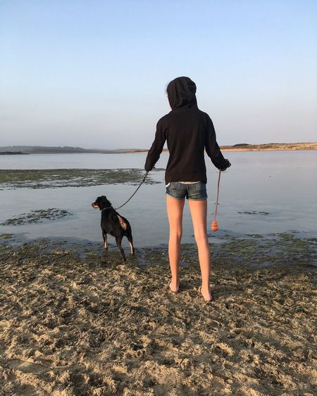 Full length rear view of woman with dog at beach against clear sky