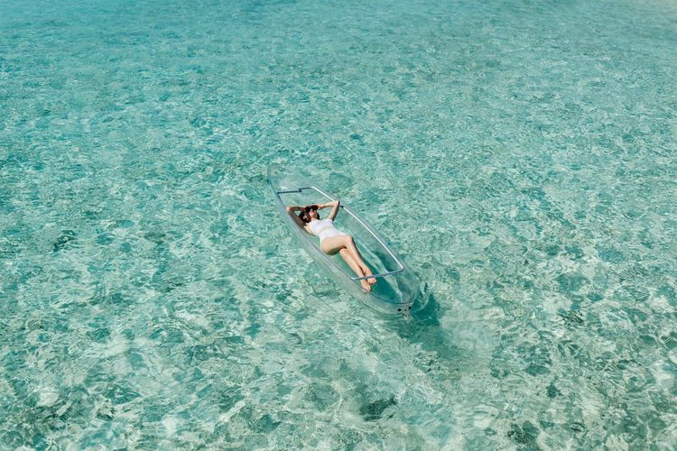 High Angle View Of Young Woman Lying In Boat On Sea During Sunny Day