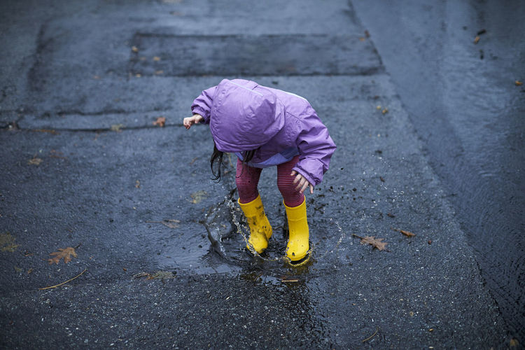High angle view of girl standing on wet street