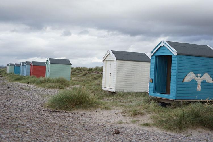 Beach hut on field against sky
