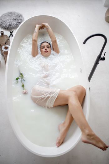 High angle view of woman lying in bathtub