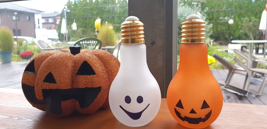 Close-up of light bulbs and jack o lantern on table