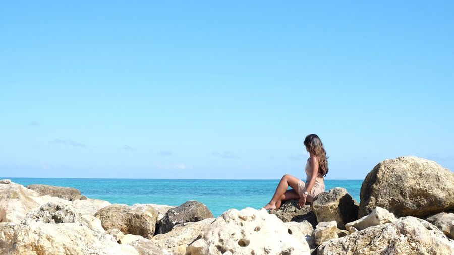 Woman looking at view of sea while sitting on rocks against sky