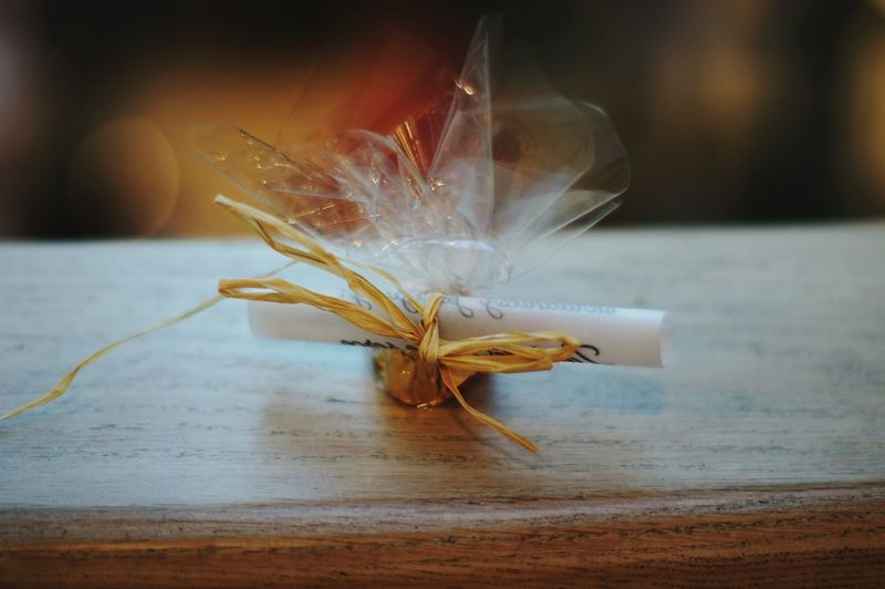Close-up of gift with message tied up with ribbon on table
